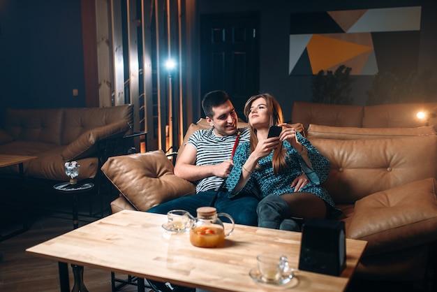 Coppia giovane fumare narghilè sul divano in pelle