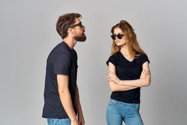 Una giovane coppia che socializza insieme posando uno sfondo chiaro di moda
