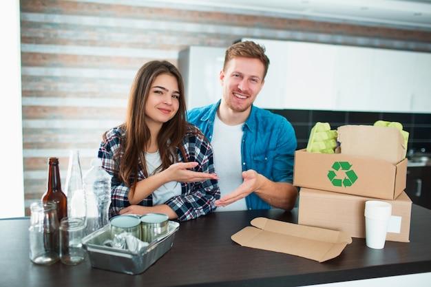 Una giovane coppia ordina i rifiuti in cucina. il giovane e la donna stanno ordinando i riciclabili in cucina. ci sono cartone, carta, ferro, plastica e vetro e altri materiali che possono essere riciclati.