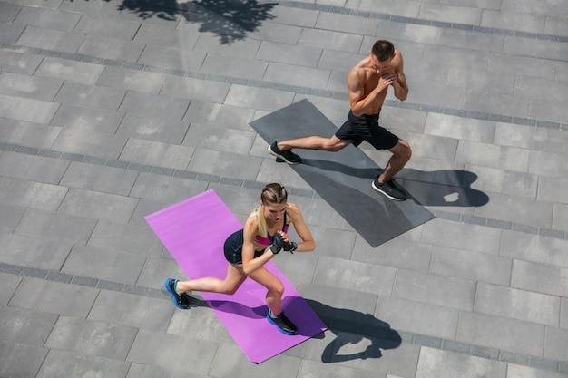 Giovane coppia in abbigliamento sportivo che fa allenamento mattutino all'aperto, stile di vita sano