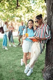 Giovani coppie che stanno sotto il grande albero nel cortile dell'università