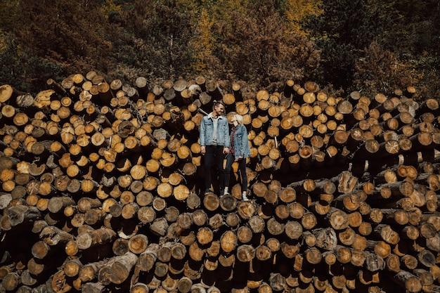 Coppia giovane in piedi su legna da ardere nella foresta con un bellissimo paesaggio autunnale