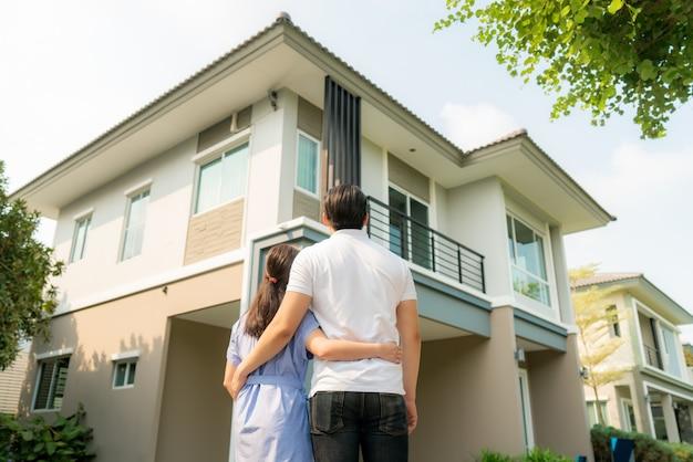 Giovani coppie che stanno e che abbracciano insieme che sembrano felici davanti alla loro nuova casa