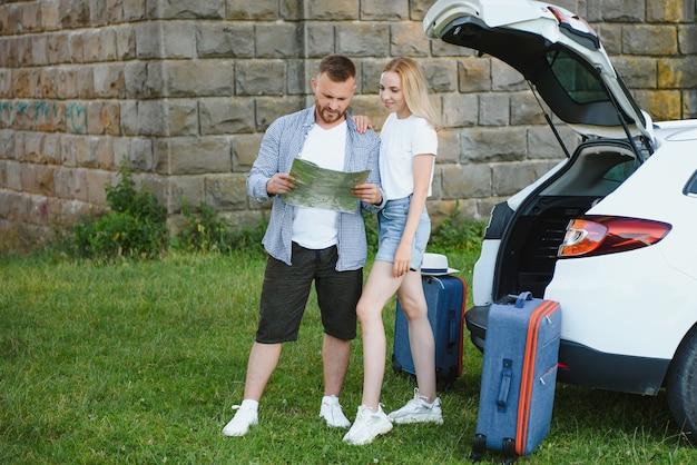 Giovane coppia in piedi vicino al bagagliaio dell'auto aperto con le valigie, guardando la telecamera, all'aperto