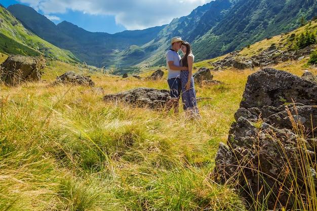 Giovane coppia in piedi vicino a una roccia di fronte allo sfondo di alte montagne in romania.