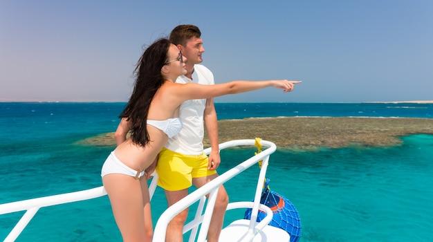 Giovane coppia in piedi sul naso dello yacht in una giornata di sole estivo, ragazza indica a mano, brezza in via di sviluppo dei capelli, bellissimo mare turchese sullo sfondo