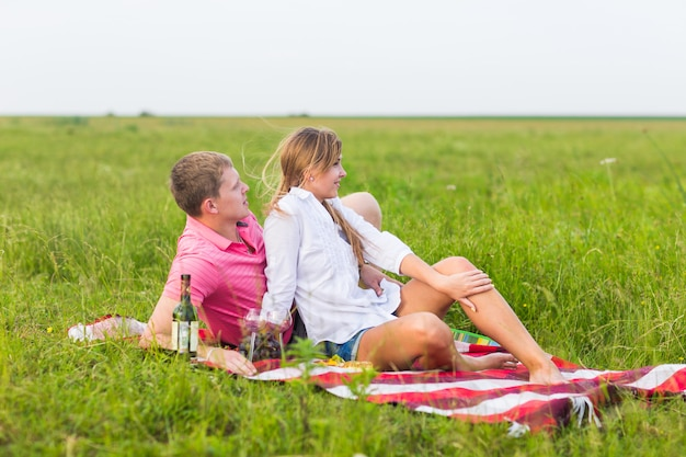 Giovane coppia in prato estivo, uomo e donna con picnic romantico.