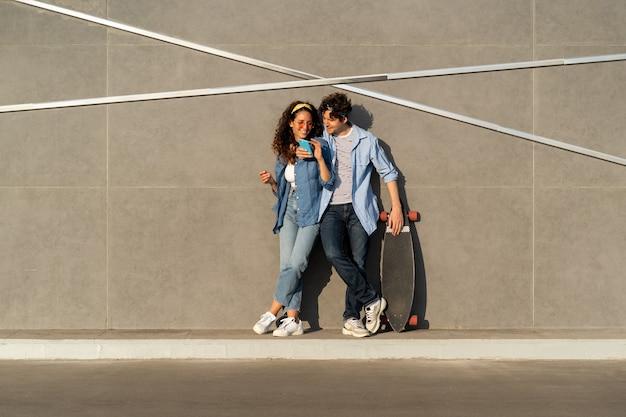 Una giovane coppia naviga nell'app dei social media sullo smartphone e guarda video online all'aperto utilizzando internet wireless
