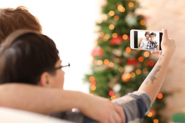 Giovani coppie che prendono selfie all'interno, primo piano