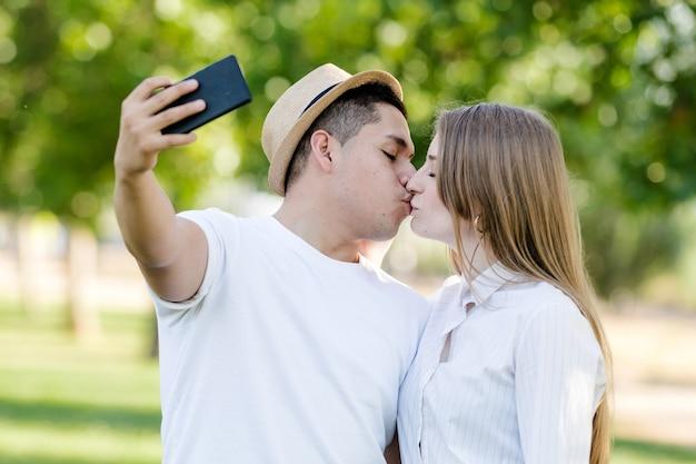 Giovani coppie che catturano un selfie sul loro cellulare nel parco