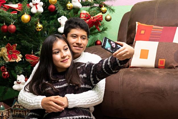 Una giovane coppia che si fa un selfie davanti all'albero di natale a casa dei nonni