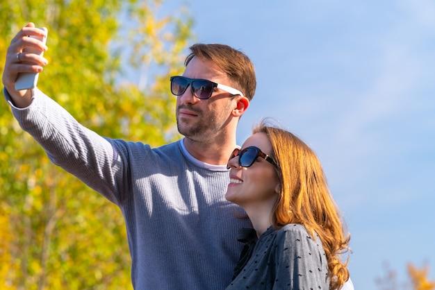Coppia giovane prendendo il loro selfie su un telefono cellulare all'aperto in autunno in un parco o in un giardino