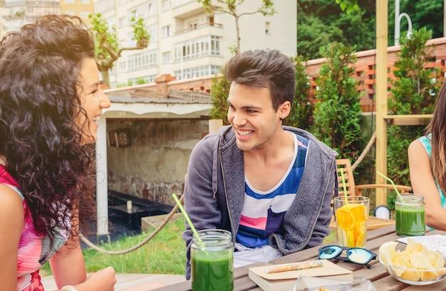 Giovani coppie che parlano e ridono intorno al tavolo con bevande salutari in una giornata estiva di svago all'aperto