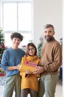 Coppia giovane e la loro graziosa figlia adolescente che tengono scatole regalo con regali mentre sono in piedi contro l'albero di natale decorato nel soggiorno