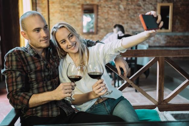 Coppia giovane brindisi con bicchieri di vino tenendo fuori un selfie.
