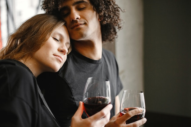 Giovani coppie che tengono insieme i bicchieri di vino.