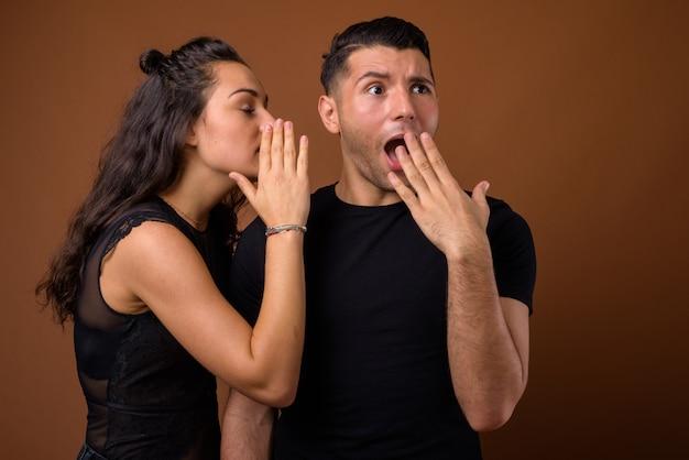 Giovane coppia insieme e innamorata contro il muro marrone