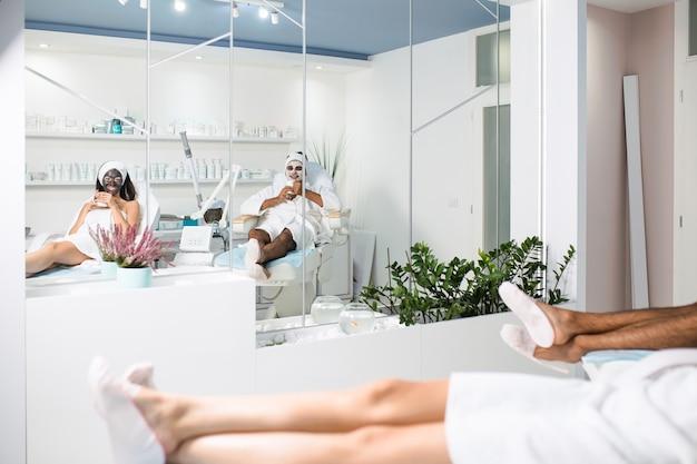 Giovane coppia che riceve insieme una maschera facciale con effetti ringiovanenti nel salone di bellezza spa.