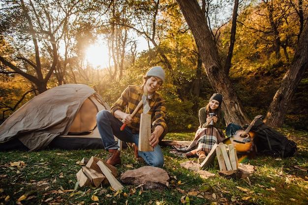 La giovane coppia di turisti sta esplorando insieme nuovi posti. bell'uomo che taglia legna con l'ascia. la donna attraente beve il tè e si siede sul ceppo