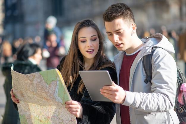 Coppia giovane di turisti in possesso di una mappa a milano, italy