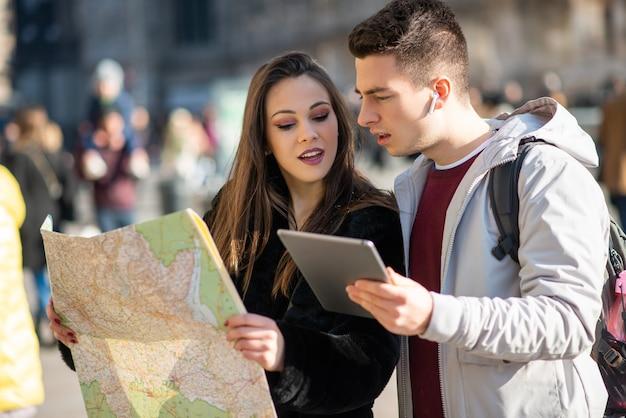 Giovane coppia di turisti in possesso di una mappa e di un tablet a milano, italia