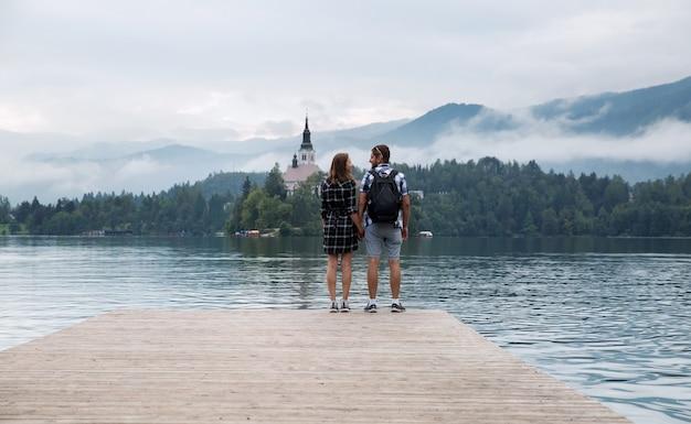 Coppia giovane di turisti innamorati sul lago di bled slovenia autunno in europa