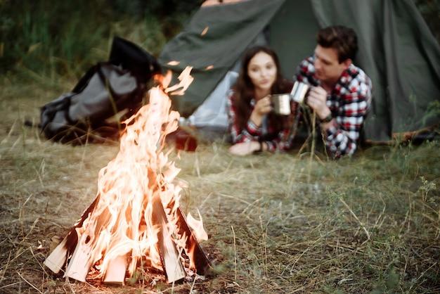 Giovane coppia di turisti uomo e donna che riposa in un campeggio, che riposa da un falò e una tenda verde in natura