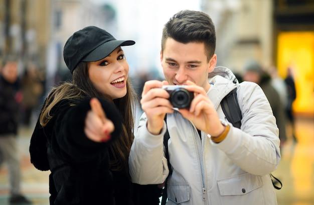 Giovani coppie di turisti che prendono le immagini nella città