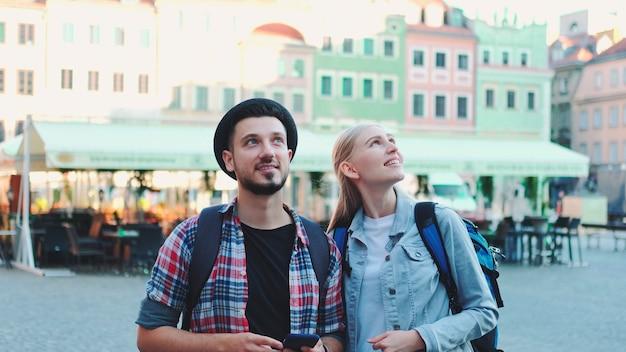 Giovane coppia di turisti che utilizzano smartphone e ammirano gli splendidi dintorni