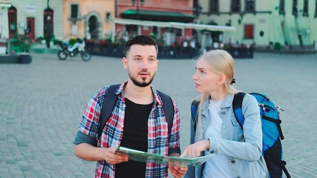Giovane coppia di turisti con mappa in cerca di un nuovo luogo storico nel centro della città camminano e f...