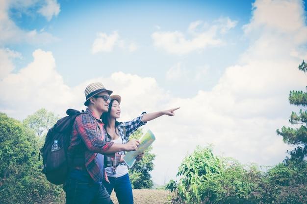 Giovani coppie turisti con mappa nel parco. avventura.