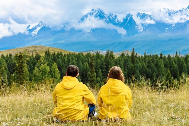 Giovani coppie di turisti in impermeabili gialli si siedono e guardano le montagne alpine innevate. concetto di viaggio e vacanza