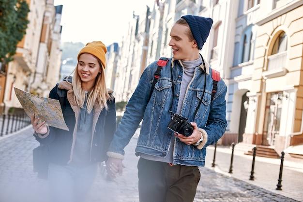 Una giovane coppia di blogger di viaggi sta cercando di navigare con la mappa in una città sconosciuta