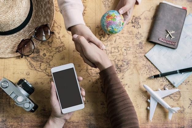 Viaggiatore giovane coppia pianificazione viaggio di vacanza e ricerca di informazioni o prenotazione hotel su uno smart phone