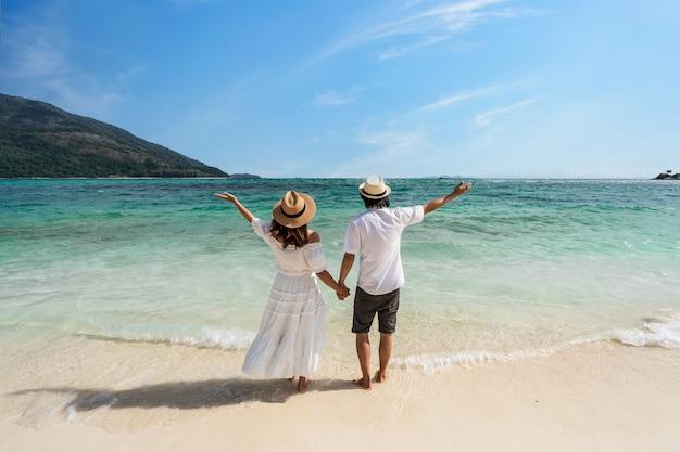 Giovane coppia viaggiatrice che si rilassa e si diverte in una bellissima spiaggia tropicale di sabbia bianca con schiuma d'onda e mare trasparente, vacanze estive e concetto di viaggio