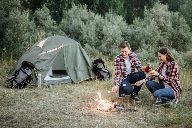 Giovane coppia di viaggiatori patatine fritte salsicce in natura