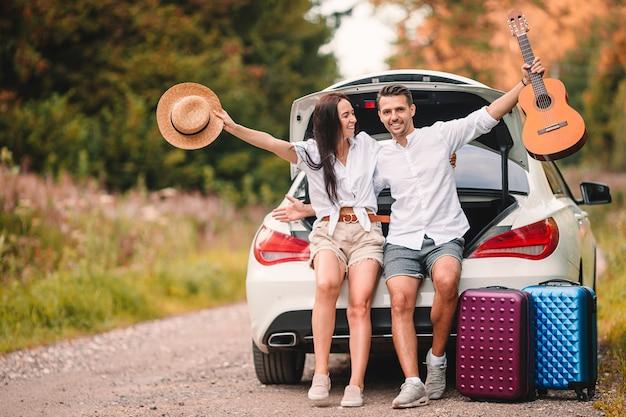 Coppia giovane viaggiatori seduti nel bagagliaio di un'auto in vacanza estiva in auto