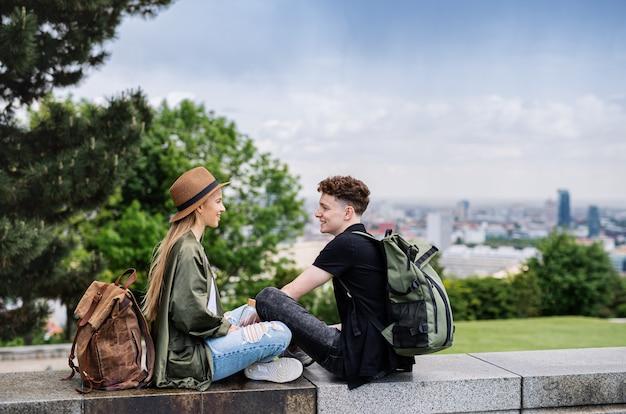 Giovani coppie di viaggiatori con mappa in città in vacanza, riposo e pianificazione.
