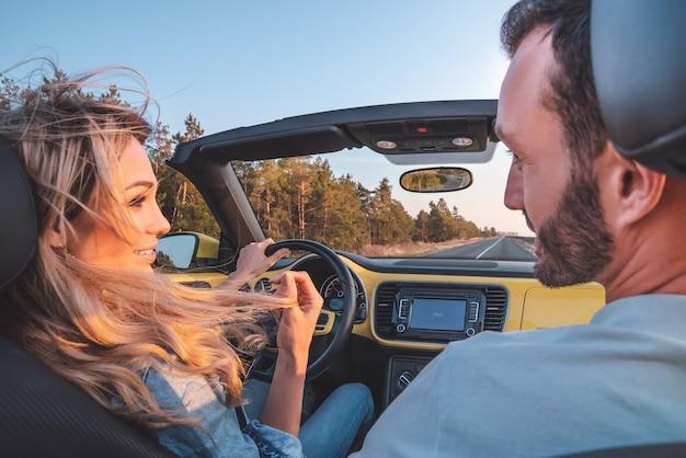 La giovane coppia che viaggia in cabriolet