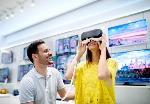 Giovani coppie che provano sugli occhiali di protezione di realtà virtuale 3d. divertirsi provando nuove tecnologie. avventura virtuale.