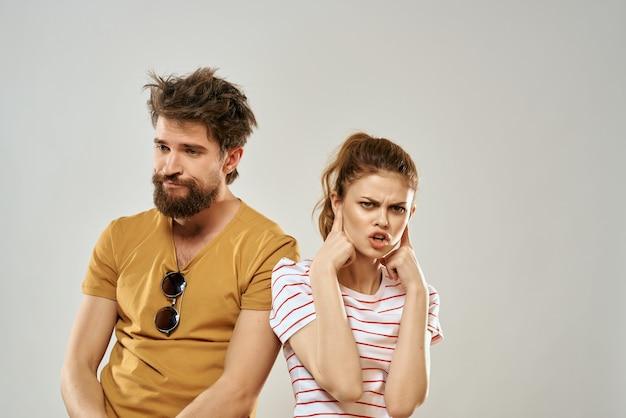 Giovane coppia in studio familiare di emozioni di magliette