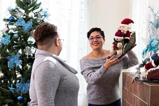 Una giovane coppia di due donne che decorano insieme la loro casa a natale