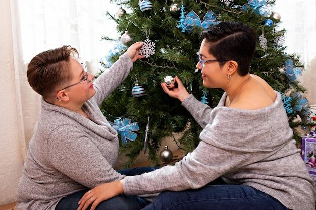 Una giovane coppia di due donne che si abbracciano, decorando insieme l'albero di natale