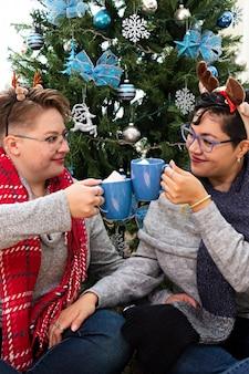 Una giovane coppia di due donne sedute davanti all'albero di natale che bevono cioccolata calda
