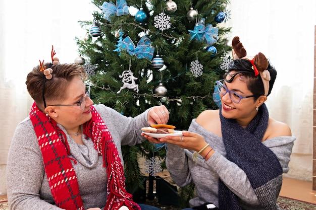 Una giovane coppia di due donne sedute davanti all'albero di natale che mangiano biscotti di natale