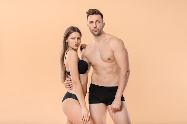 Giovane coppia in biancheria intima su sfondo colorato