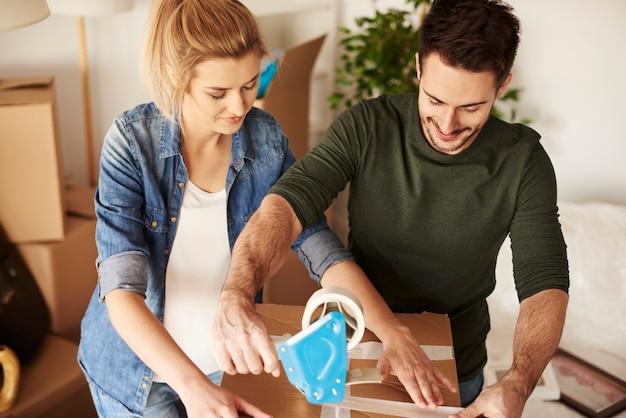 Giovane coppia che disimballa le scatole del trasloco nel nuovo appartamento