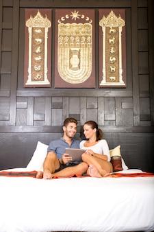 Giovani coppie che utilizzano un tablet pc in una stanza d'albergo asiatica mentre giaceva sul letto.