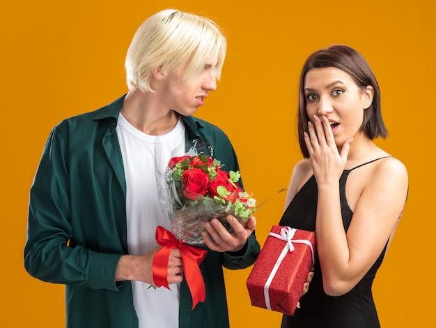 Giovane coppia il giorno di san valentino uomo che tiene il secchio di fiori guardando la donna e la donna preoccupata che tiene la mano sulla bocca tenendo il pacchetto regalo guardando la parte anteriore isolata sul muro arancione