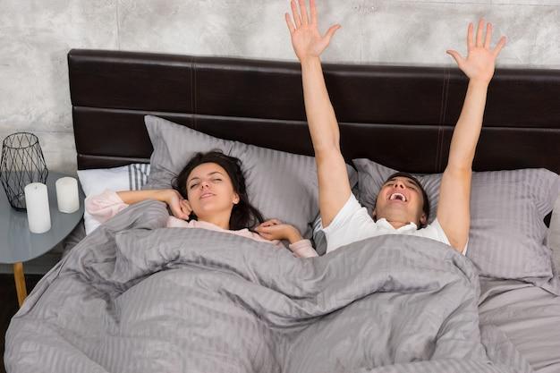 La giovane coppia si sveglia e si allunga mentre è sdraiata a letto, indossando un pigiama in camera da letto in stile loft con colori grigi